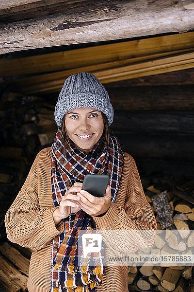 Junge Frau mit Smartphone in der Nähe eines Holzstapels