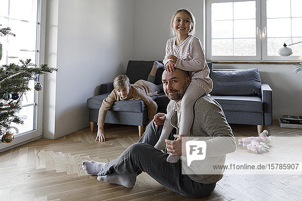 Porträt eines reifen Mannes  der zu Hause auf dem Boden sitzt und mit seiner kleinen Tochter spielt