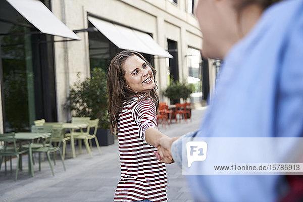 Glückliche Frau Hand in Hand mit dem Mann in der Stadt