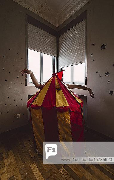 Person  die sich hinter einem Spielzeugzelt in einem leeren Raum versteckt