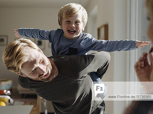 Glücklicher Vater trägt Sohn huckepack zu Hause