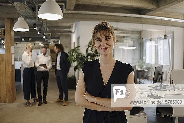 Porträt einer selbstbewussten Geschäftsfrau im Amt mit Kollegen im Hintergrund