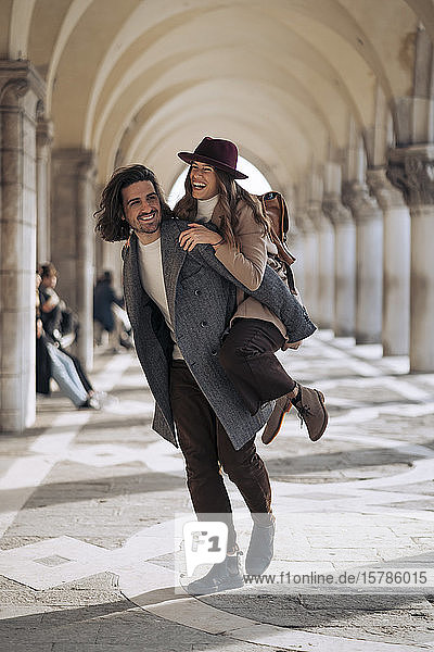 Junger Mann nimmt seine Freundin huckepack in der Stadt Venedig  Italien