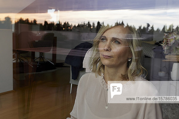 Portrait of blond woman behind windowpane at home