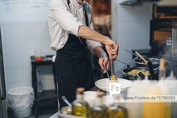 Chefkoch bereitet ein Nudelgericht in der traditionellen italienischen Restaurantküche zu