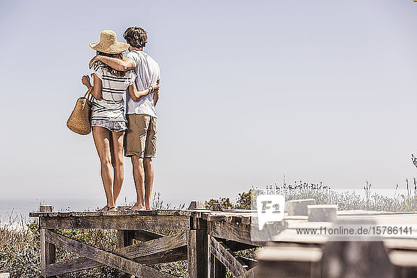 Young couple standing on a boardwalk at the coast looking at view