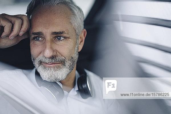 Porträt eines lächelnden reifen Geschäftsmannes in seinem Auto