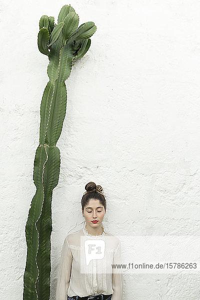 Bildnis einer jungen Frau mit geschlossenen Augen neben einer großen Sukkulente stehend