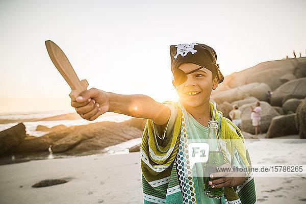 Junge als Pirat verkleidet am Strand bei Sonnenuntergang