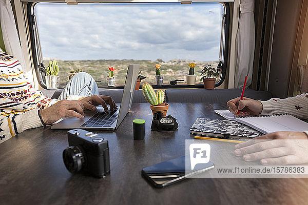 Schrägansicht eines in einem Wohnmobil arbeitenden Paares  Es Mercadal  Menorca  Spanien