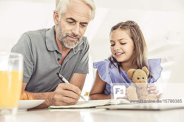 Girl watching father taking notes at home