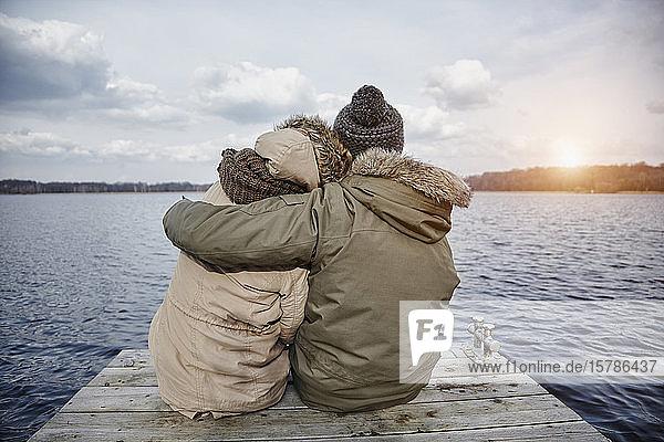 Rückenansicht eines jungen verliebten Paares  das auf einem Steg sitzt und im Winter auf den See schaut