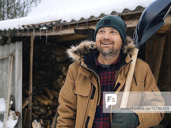 Porträt eines lächelnden Mannes mit Schneeschaufel