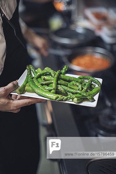 Chefkoch hält Teller mit grünem Spargel in Restaurantküche