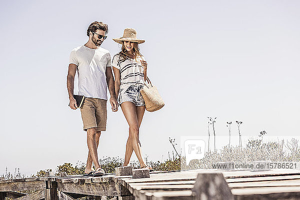 Young couple walking along a boardwalk from the beach