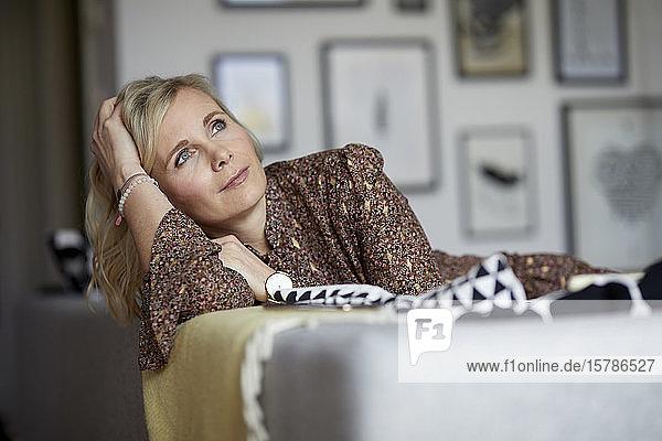 Blond woman relaxing at home sitting on couch