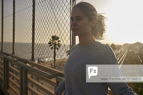 Sportliche junge Frau steht bei Sonnenschein auf einer Brücke