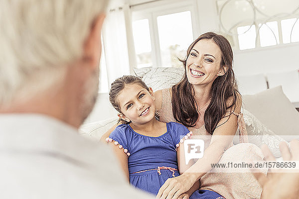 Smiling woman with daighter looking at man on couch in living room