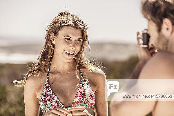 Mann fotografiert eine junge Frau im Bikini