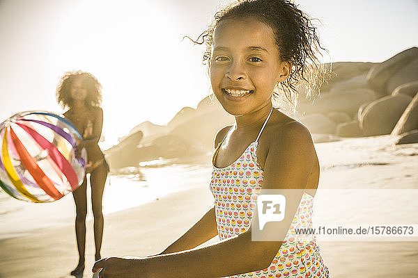 Porträt eines glücklichen Mädchens  das mit seiner Mutter am Strand spielt