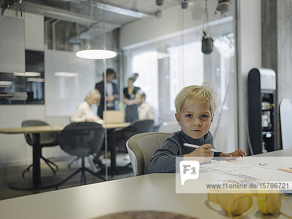 Portrait of boy painting in office with business team having a meeting