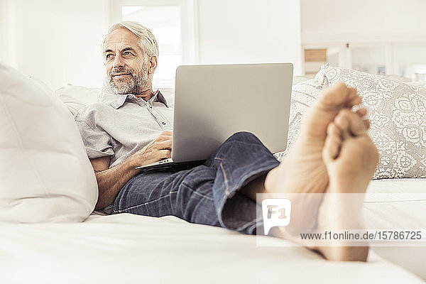 Mature man using laptop on couch at home