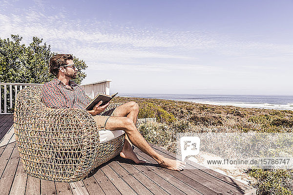 Man reading a book on a deck at the coast