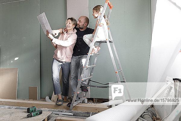 Familie auf der Baustelle zu Hause studiert Plan
