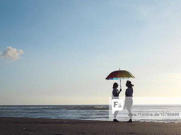 Zwei Frauen mit Sonnenschirm stehen in der Abenddämmerung am Strand  Kedungu Beach  Bali  Indonesien