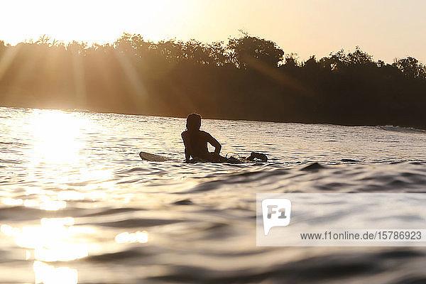 Weibliche Surferin bei Sonnenuntergang  Bali  Indonesien