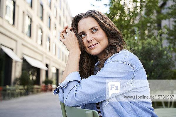 Porträt einer lächelnden brünetten Frau  die auf einem Stuhl in der Stadt sitzt