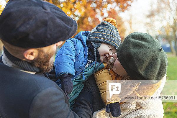 Glückliches  liebevolles Paar mit kleinem Sohn im Park