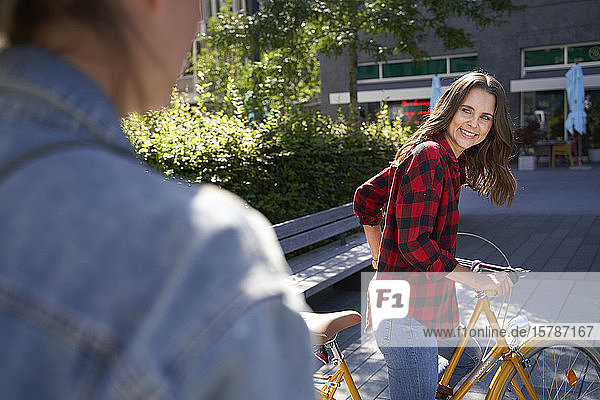 Brunette woman with bicycle in the city turning round