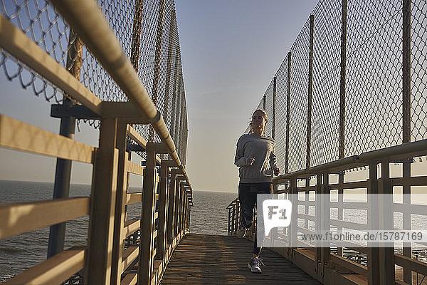 Junge Frau rennt auf einem Steg am Meer