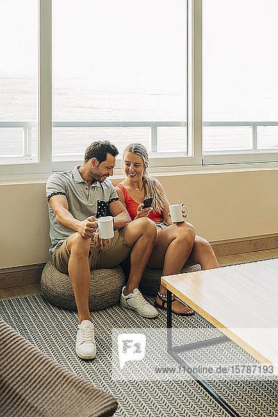 Glückliches Paar sitzt zu Hause am Fenster mit Kaffeetassen und Handy