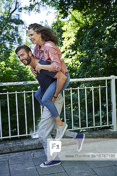 Happy man running and carrying woman piggyback