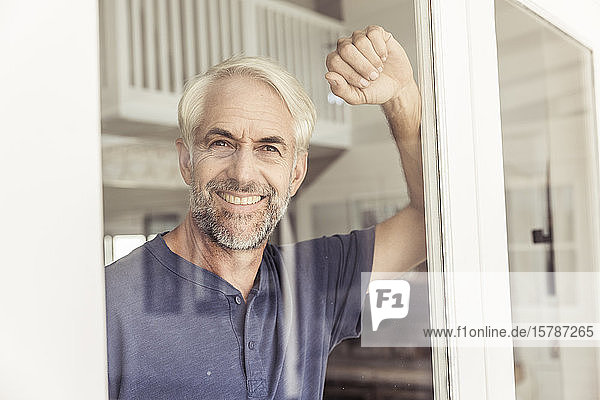 Portrait of smiling mature man looking out of window