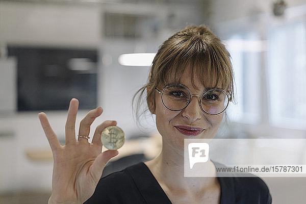 Porträt einer Geschäftsfrau  die Bitcoin im Amt hält