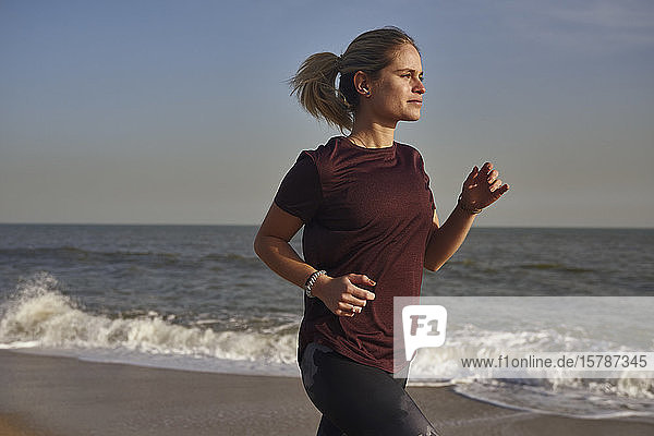 Junge Frau rennt am Strand
