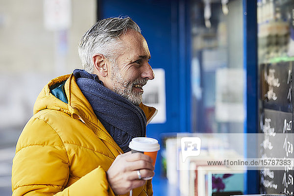 Smiling mature man at a stall with takeaway coffee