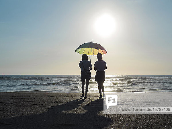 Two women with sunshade walking on the beach at evening twilight  Kedungu beach  Bali  Indonesia