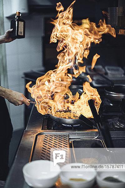 Koch  der ein Flammengericht am Gasherd in der Restaurantküche zubereitet