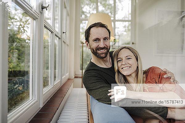 Glückliches Paar auf der Couch sitzend  mit Arns um sich herum  lächelnd