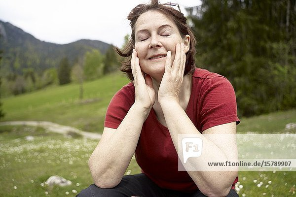 Mature woman in countryside with eyes closed. Bad Tölz  Upper bavaria  Germany.