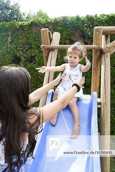 Young girl helps her little sister going down the slide.
