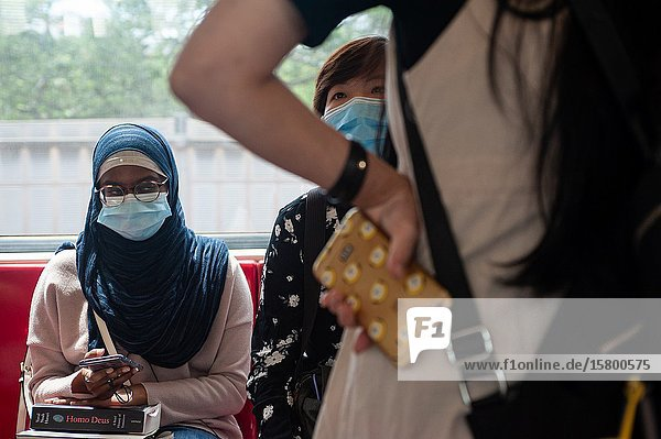Singapore  Republic of Singapore  Asia - Passengers on a metro train wear protective masks to prevent an infection with the coronavirus.