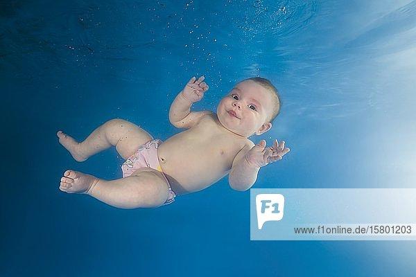Kleines Mädchen schwimmt seitlich in einem Pool unter Wasser  Russland  Europa