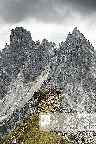 Bergsteiger mit roter Jacke steht auf einem Grat  hinten Berggipfel und spitze Felsen  Wolkenhimmel  Cimon di Croda Liscia und Cadini-Gruppe  Auronzo di Cadore  Belluno  Italien  Europa