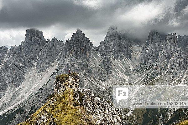 Bergsteiger mit roter Jacke steht auf einem Grat  hinten Berggipfel und spitze Felsen  dramatische Wolken  Cimon di Croda Liscia und Cadini-Gruppe  Auronzo di Cadore  Belluno  Italien  Europa