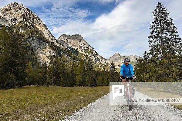 Fahrradfahrer  Mountainbiker radelt auf Schotterweg  Karwendeltal  Weg zum Karwendelhaus  Tirol  Österreich  Europa